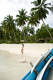INDONESIA, Mentawai Islands, Kandui Surf Resort, young woman walking on beach with palm trees in the background