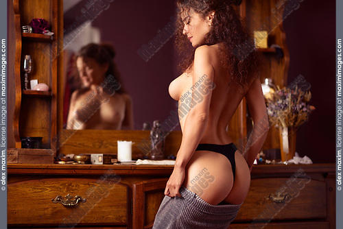 Sensual erotic portrait of a sexy beautiful topless half naked woman dressing up in front of a mirror