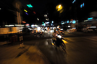 A woman on a bicycle casually pedals through busy night-time traffic in Ho Chi Minh City (Saigon), Vietnam