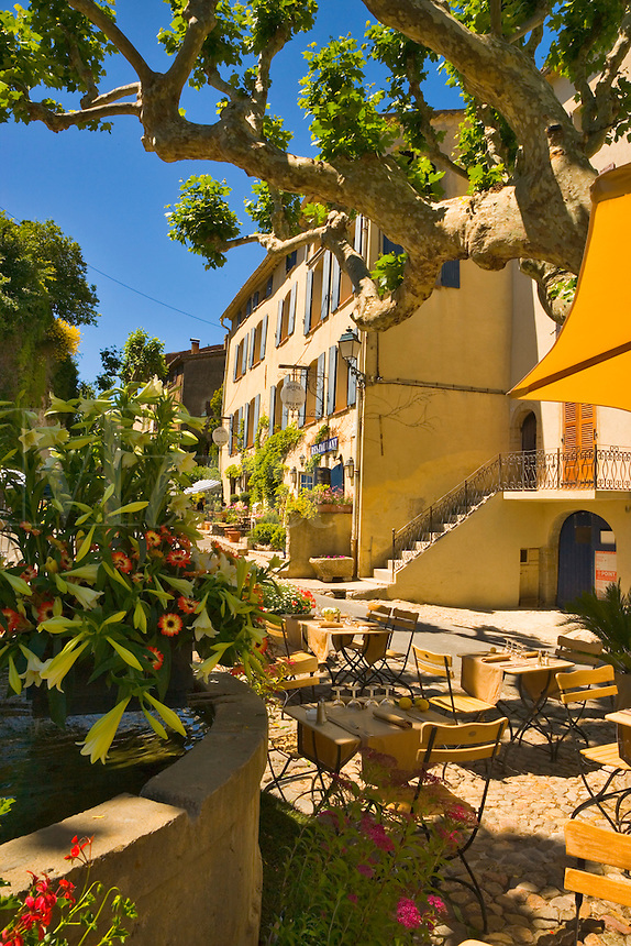 Hotel des Deux Rocs and restaurant around the fountain in the village of Seillans during the Flower Festival. Var, Provence, France.