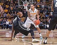 California's Justin Cobbs finds his path while Colorado's Jaron Hopkins slips during a game at Haas Pavilion in Berkeley, California on March 8th, 2014. California defeated Colorado 66 - 65