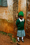 A timid student sulks at the Hamomi Children's Centre in Nairobi, Kenya.  Her entire day was ruined when she found out too late they had been handing out free socks and shoes at lunch.
