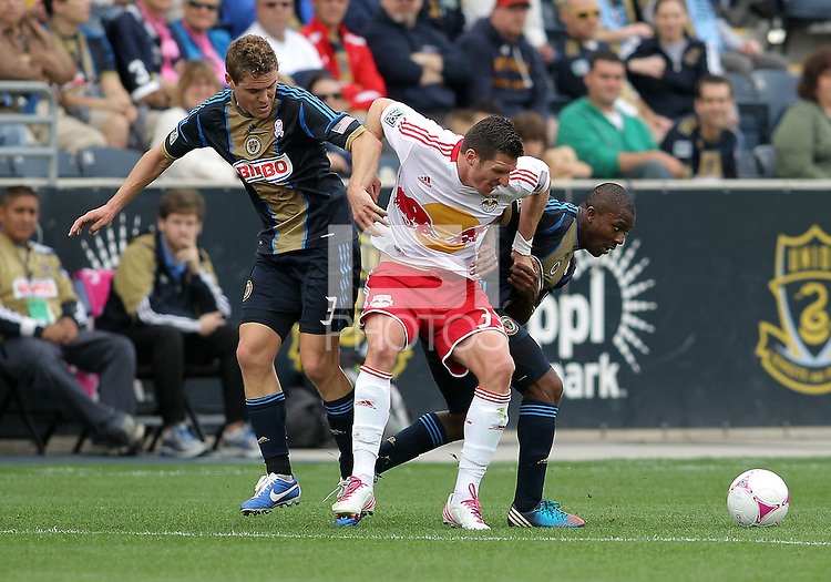CHESTER, PA - OCTOBER 27, 2012:  Michael Lahoud (13) and Chris Albright (3) of the Philadelphia Union close in on  Kenny Cooper (33)  of the New York Red Bulls during an MLS match at PPL Park in Chester, PA. on October 27. Red Bulls won 3-0.
