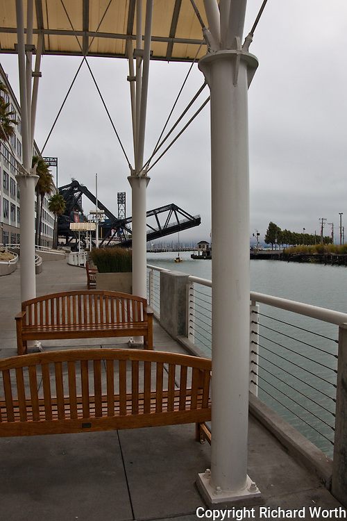 Covered benches behind a business complex with the rising Lefty O'Doul drawbridge opening to allow passage of a sailboat making its way from Mission Creek into China Basin, or as some call it, McCovey Cove.