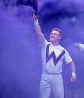 A Husky cheerleader gets the purple smoke going.