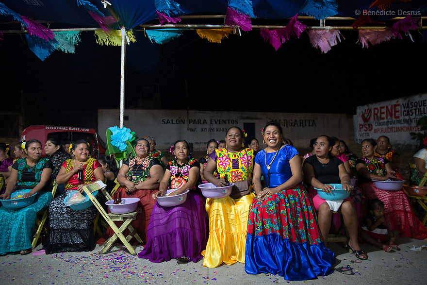 "Darina Guerra Carballo (R), 32, sitting with her mother Rosalia (L) and her older muxe sister Andrea Guerra Carballo (C), at a traditional birthday party of a close family friend in Juchitán de Zaragoza, Mexico on October 4, 2018. Darina is a muxe from Juchitán de Zaragoza, Mexico. She works as a dressmaker and lives with her boyfriend Jesús Gómez Reyes, 29. Having an older sibling who is a muxe made life easier for her. ""Deep down, I feel like a woman but I recognise I am a muxe,"" she says. She has been dressing as a woman for a decade. ""My dad still calls me by my real name. He doesn't make me do men's work but he can't bring himself to call me by a girl's name."" Born men, but often living as women, muxe occupy a traditional role in indigenous Zapotec culture that goes beyond identifying as gay. Photo by Bénédicte Desrus"