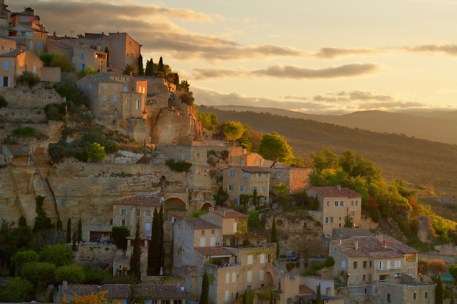 Sunset on Gordes, France. Gordes is a very beautiful old village, perched on the southern edge of the high Plateau de Vaucluse. The stone buildings built in tight against the base of the cliffs are made of an beige stone that glows orange in the morning sun.