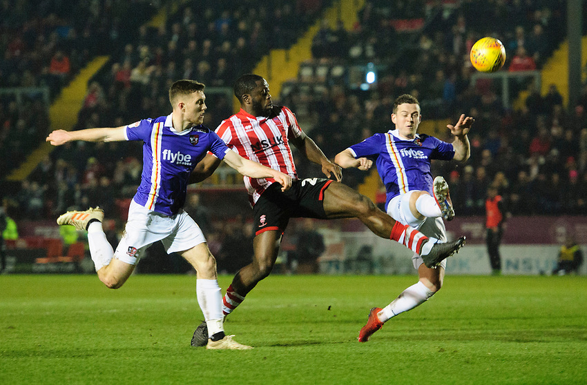 Lincoln City's John Akinde vies for possession with Exeter City's Dara O'Shea, left, and Exeter City's Pierce Sweeney<br /> <br /> Photographer Chris Vaughan/CameraSport<br /> <br /> The EFL Sky Bet League Two - Lincoln City v Exeter City - Tuesday 26th February 2019 - Sincil Bank - Lincoln<br /> <br /> World Copyright © 2019 CameraSport. All rights reserved. 43 Linden Ave. Countesthorpe. Leicester. England. LE8 5PG - Tel: +44 (0) 116 277 4147 - admin@camerasport.com - www.camerasport.com