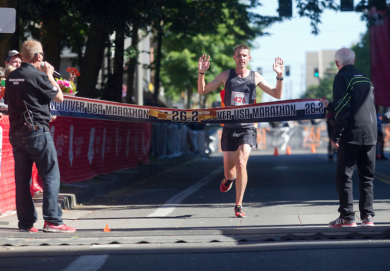 Brent Corbitt, the winner Vancouver Marathon, crosses the finish line in downtown Vancouver Sunday June 19 2016. Corbitt, from Arkansas, reported that this was his first marathon.  (Photo by Natalie Behring for the Columbian)
