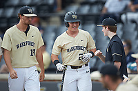 Chris Lanzilli (24) of the Wake Forest Demon Deacons is all smiles as he returns to the dugout after scoring a run during the game against the against the Virginia Cavaliers at David F. Couch Ballpark on May 19, 2018 in  Winston-Salem, North Carolina. The Demon Deacons defeated the Cavaliers 18-12. (Brian Westerholt/Four Seam Images)