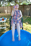 Older womanin backyard with feet in small pool with fan and drinking ice tea on a hot summer day