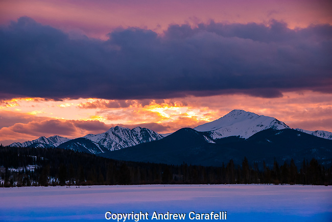 A late spring sunset near Winter Park, Colorado brings vibrant hues of orange and purple to the sky.