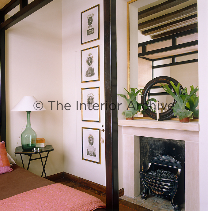 In the intimate master bedroom a feeling of space is created by hanging a large mirror over the fireplace