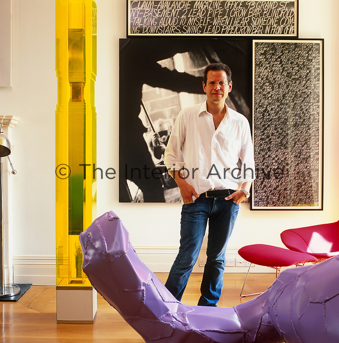Kenny Schachter standing in his living room surrounded by a collection of contemporary art