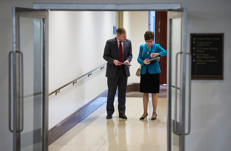 UNITED STATES - MAY 14: Sen. Susan Collins, R-Maine, checks her watch as she speaks with staff in the hallway leading from the Capitol to the CVC on Tuesday, May 14, 2013 . (Photo By Bill Clark/CQ Roll Call)