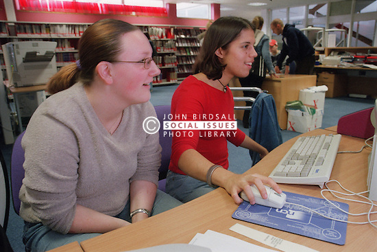 Teenage girl with physical disability using computer with friend in college library,