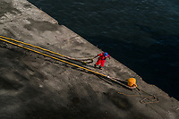 A dock worker pulls a large rope to secure a cruise ship