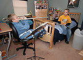 Sam Salem 12 of Telford, Pa. (left), practices the trombone on a cold Thursday March 2, 2006, while his twin brother Jake (right) practices his guitar before his lesson. The American flag hangs in the boys bedroom. Three of the Salem children play musical instruments. Sam the trombone, Jake the guitar and Julianne the piano. The Salem children, 3 sets of twins, are from Nevel, Russia. Sophia and twin Joseph were adopted at 11 months of age by Hythem and his wife Lisa. The other twins, Selene and Julianne 13 along with Sam and Jake, were adopted just 20 months ago. All children are thriving in school, socially and physically. photo by jane therese