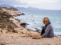 Spain, ESP, Canary Islands, Fuerteventura, Istmo de La Pared, 2012Oct13: A female tourist sits at the coast of the Istmo de La Pared.