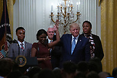 United States President Donald J. Trump raises the arm of a woman after she led a prayer at the Young Black Leadership Summit in the East Room of the White House in Washington D.C., U.S. on October 4, 2019.<br />  <br /> Credit: Stefani Reynolds / CNP