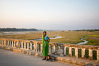 A woman stands on the Mechi bridge which connects India and Nepal near the Panitanki border post. The border point is one of the main smuggling routes for tiger parts trafficking between India and China.
