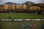 The players are framed by the Eildon hills in the background during the first-half as Gala Fairydean Rovers (in red) host Gretna 2008 in a Scottish Lowland League match at Netherdale, Galashiels. The home club were established in 2013 through a merger of Gala Fairydean, one of Scotland's most successful non-League clubs, and local amateur club Gala Rovers. The visitors were a 'phoenix' club set up in the wake of the collapse of the original club, which had competed for a short time in the 2000s before going bankrupt. The home aside won this encounter 4-1 watched by a crowd of 120 at a stadium which features one of the country's most notable stands, a listed building constructed in 1964 but at the time of this fixture closed to spectators on safety grounds.