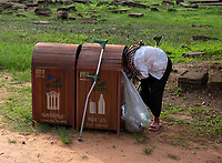 A handicapped women, Nun is collecting plastic from a bin near the Bayon Temple in the Angkor area, Cambodia