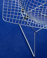 A classic Bertoia armchair against a bright blue carpet