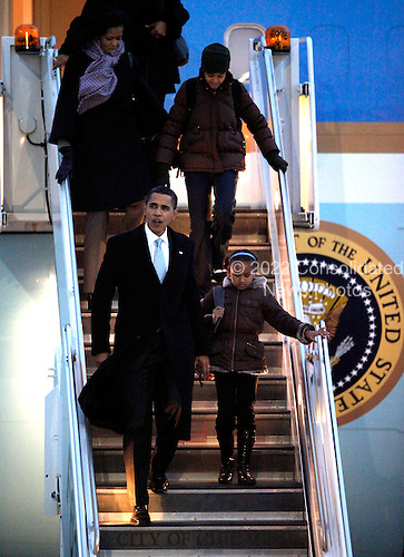 Chicago, IL - February 13, 2009 -- United States President Barack Obama (L) arrives at O'Hare International Airport with his wife Michelle (back left) and daughters Sasha (R) and Malia on Friday, February 13, 2008 in Chicago. The weekend visit to Chicago is Obama's first since the Inauguration. .Credit: Brian Kersey - Pool via CNP