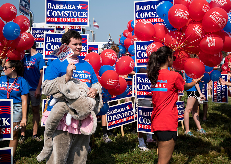 UNITED STATES - JULY 4: Dressed in a hot elephant costume, a supporter of Rep. Barbara Comstock, R-Va., fans himself as the Comstock group prepares to step off in the Leesburg Independence Day Parade in Leesburg, Va., on July 4, 2018. Comstock facing Democrat Jennifer Wexton for Virginia's 10th Congressional district seat. (Photo By Bill Clark/CQ Roll Call)