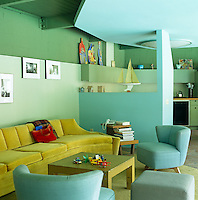 An ochre-coloured velvet sofa adds a contrasting tone to the colour of the open-plan living area