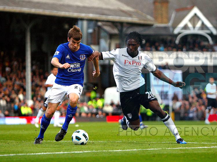 Seamus Coleman of Everton holds off Dickson Etuhu of Fulham