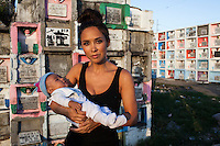 UK celebrity Myleene Klass carries a baby in a graveyard where she has come to meet underprivileged mothers and children who live in an inhabited cemetery in Paranaque City, Metro Manila, The Philippines on 18 January 2013. Photo by Suzanne Lee for Save the Children UK