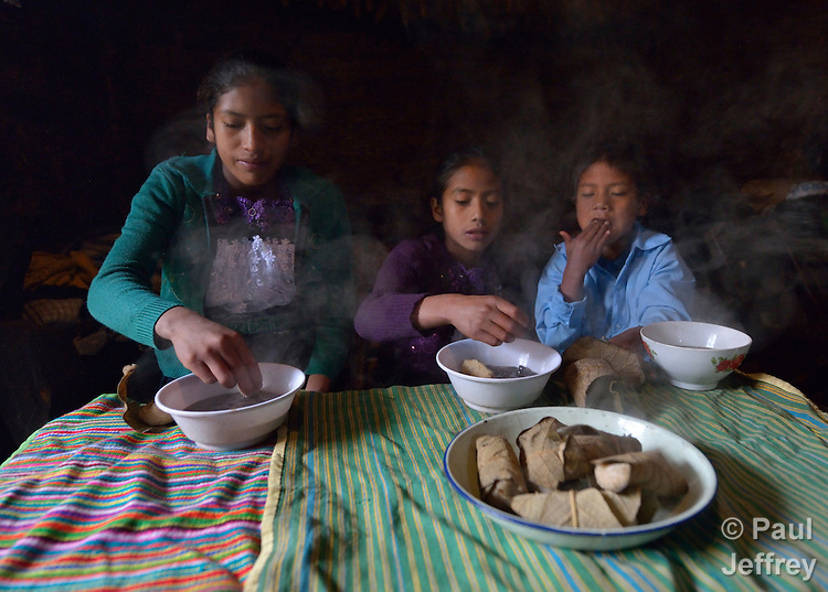 Children eat breakfast at their home in Tuixcajchis, a small Mam-speaking Maya village in Comitancillo, Guatemala. They are, from left, Griselda, 13; Lidia, 11; and Elder Diaz Vasquez, 6.