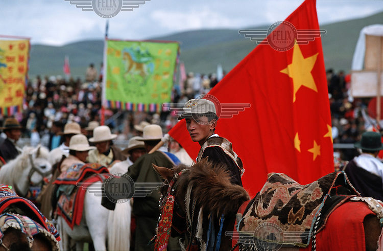 A Tibetan nomad holds a Chinese national flag during a government organized horse race.