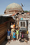 Twenty two year old Sapna Singh from Uttar Pradesh with her children  outside her home built into a Lodhi Period tomb complex at Nizamuddin in Delhi, India. The Archaeological Survey of India has been on a campaign to evict people who have illegally made the tombs their homes throughout the city in recent times but is facing stiff opposition from the residents. The area is littered with tombs that need excavation.