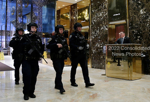 Armed NYPD police officers walk through the lobby of Trump Tower on November 29, 2016 in New York City.       <br /> Credit: John Angelillo / Pool via CNP