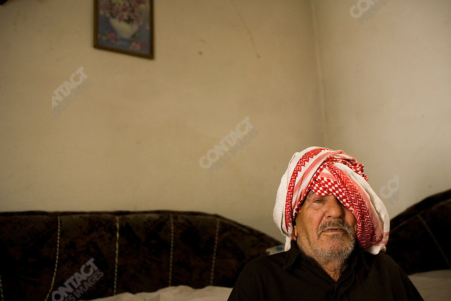 A blind man, father of 11 children and at least 6 grandchildren in the two-room apartment he shares with his wife, several sons and two of his daughters. They are Sabian Mandaean, a minority group in Iraq who have suffered extreme cases of persecution. Family members have been affected by persecution, rape, gun shot wounds, and other types of physical abuse. The children are unable to attend school. There are 19 family members living in the Hashmi Al Shemali area of Amman, Jordan. April, 2007.