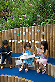 Children reading in an outdoor quiet area in the nursery garden at Wilberforce Primary School, Queens Park, North Paddington.