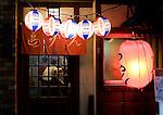 Two men enjoy food and drinks at an hole-in-the-wall eatery in Shimokitazawa, Setagaya Ward, Tokyo, Japan..Photographer: Robert Gilhooly
