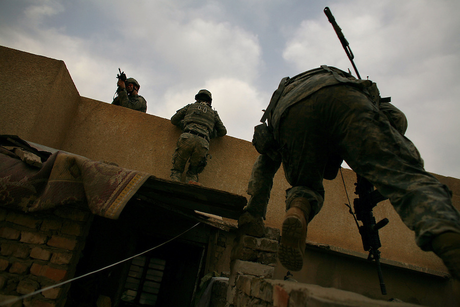 A trio of soldiers from Alpha Co. 2-12 Infantry 2nd Infantry Division move from rooftop to rooftop to avoid IEDs as they reconnoiter a portion of the Dora neighborhood in south-central Baghdad on Wednesday May 09, 2007.
