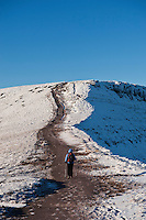Female hiker on path towards Corn Du from Pen Y Fan in winter, Brecon Beacons national park, Wales
