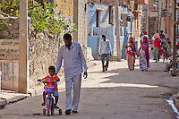Indian man with child on tricycle in the village of Narlai in Rajasthan, Northern India