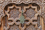 Iron door handle of 'Fatima's Hand' on a wooden, moroccan door in the medina of Marrakech, Morocco.