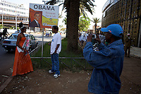 A man takes a photo of Salam ( on left )  19 years old winner of the Miss Obama beauty pagent held at the Obama Cafe owned by Alelegn Abebaw  who is on right talking to the woman  in front of his business's sign In Amhara's regional capital Bahir Dar on President Barack Obama's inauguration day, Tuesday January 20 2009..