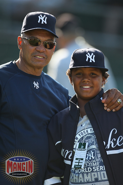 OAKLAND, CA - JULY 5:  Special assistant Reggie Jackson of the New York Yankees poses with a young friend during batting practice before the game against the Oakland Athletics at the Oakland-Alameda County Coliseum on July 5, 2010 in Oakland, California. Photo by Brad Mangin