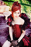 Portrait of young woman with red hair dressed in victorian style corset, sitting on stairs outdoors looking at camera