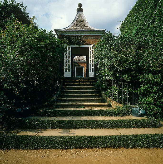 A series of stone steps lined with tall hedges rises to a garden pavilion with a curved roof in the style of a Chinese pagoda