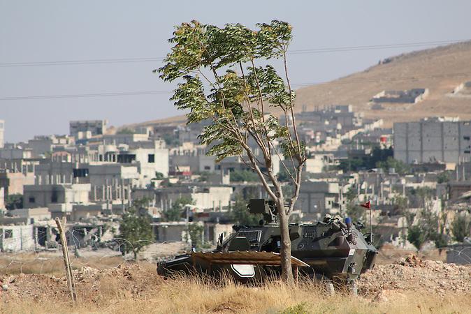 Türkische Panzer an der syrischen Grenze, im Hintergrund ist die zerstörte Stadt Kobane zu sehen. Im September 2014 erorberte die IS Terrormiliz Kobane, im Februar 2015 gelang die Befreiung, jedoch wird der Wiederaufbau noch mehrere Jahre dauern.