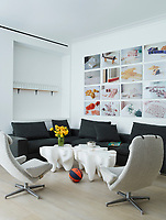 The informal living room has white walls and a wood floor. Two retro style swivel chairs and an L-shaped sofa are arranged around shaped, modular white tables.